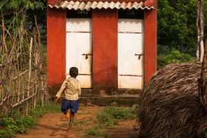 Child running towards the latrines in India